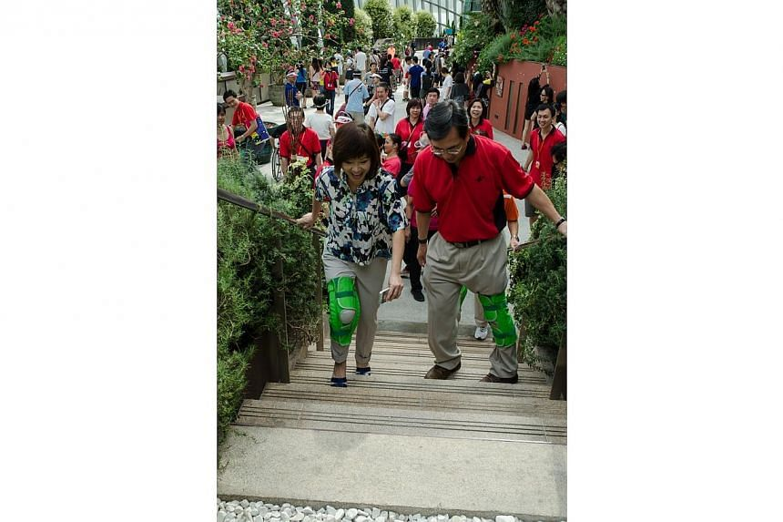 Dr Amy Khor and Dr John Keung climb up a flight of stairs with their knee restrictors. -- PHOTO: BCA