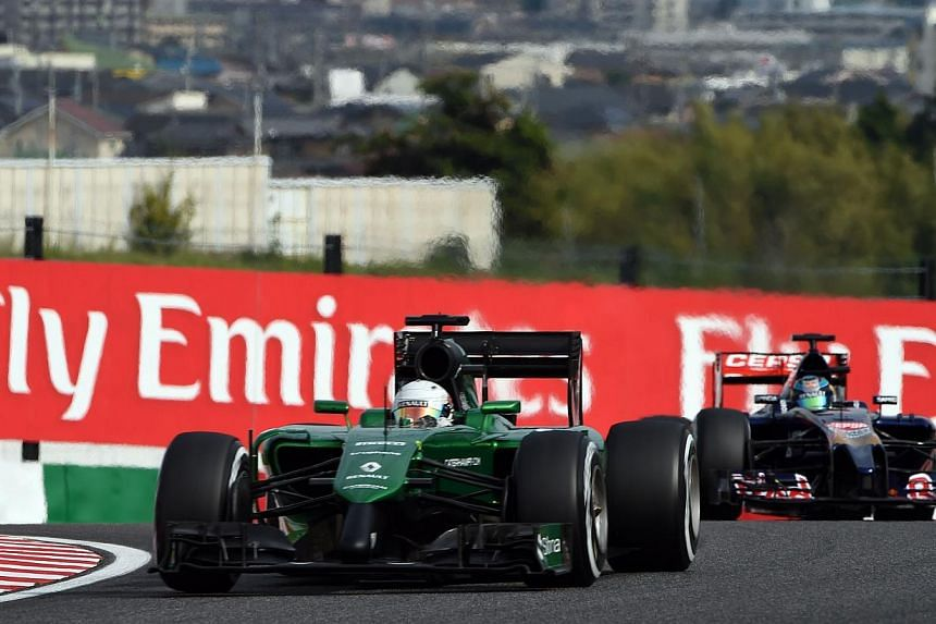 Caterham driver Kamui Kobayashi of Japan drives ahead of Toro Rosso driver Jean-Eric Vergne of France (right) during the qualifying session at the Formula One Japanese Grand Prix in Suzuka on Oct 4, 2014. Cash-strapped Caterham are pleading with fans
