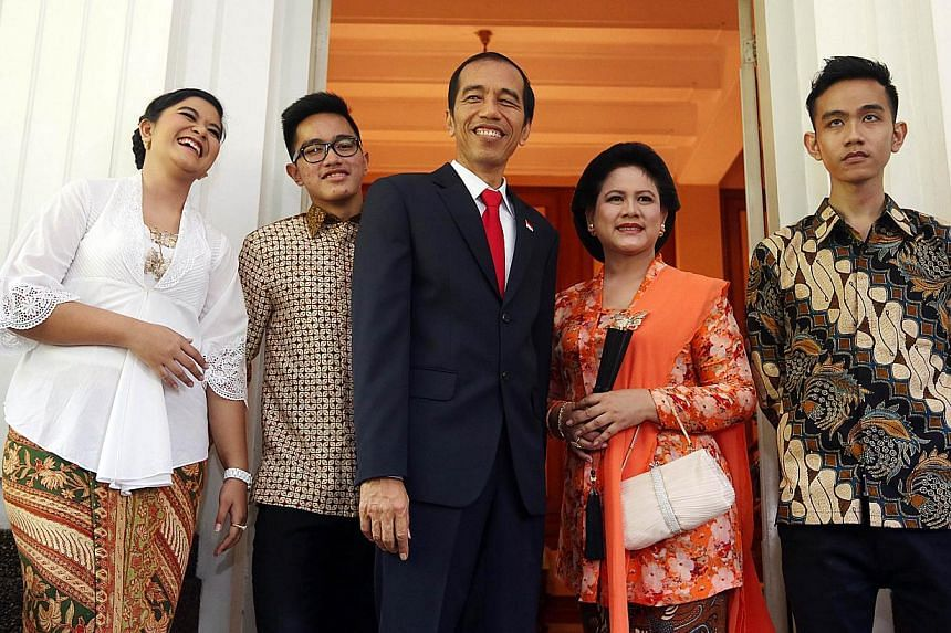 Indonesia's President Joko Widodo (centre) stands with First Lady Iriana Widodo (fourth left), son Gibran Rakabuming (fifth left), daughter Kahiyang Ayu (left) and Kaesang Pangarep (second left) for an unofficial portrait of Indonesia's First Family