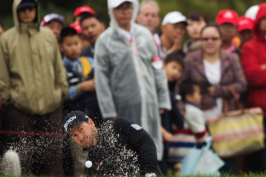 "Graeme McDowell of Northern Ireland hits out of the bunker at the second hole during the third day of the WGC-HSBC Champions Golf tournament in Shanghai on Nov 8, 2014. McDowell lashed the snail-like pace of play on Saturday as ""ridiculous"" afte"
