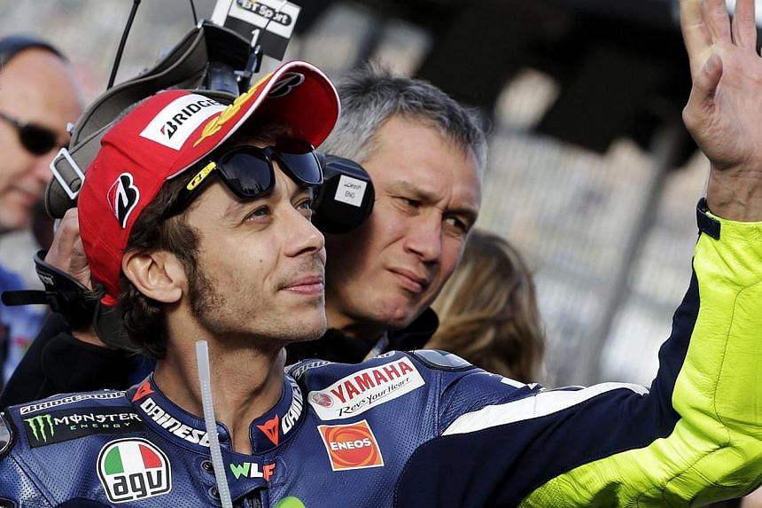 Yamaha MotoGP rider Valentino Rossi of Italy celebrates his pole position after the qualifying session of the Valencia Motorcycle Grand Prix at the Ricardo Tormo racetrack in Cheste, near Valencia, Spain on Nov 8, 2014. -- PHOTO: REUTERS