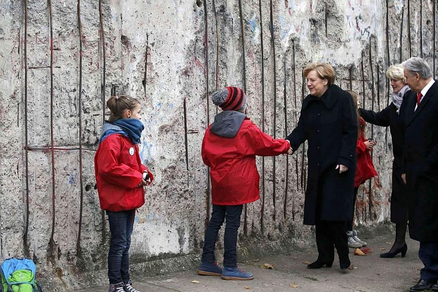 German Chancellor Angela Merkel (centre) shakes hands with children as she walks along a preserved segment of the Berlin Wall with Federal Government Commissioner for Culture Monika Gruetters (third, right), Berlin Mayor Klaus Wowereit (second, right
