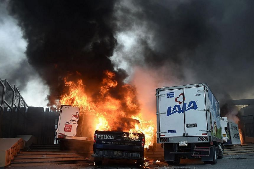 View of burning vehicles during a protest demanding for justice in the case of the 43 missing students, outside the State Government headquarters in Chilpancingo, Mexico, on Nov 8, 2014. -- PHOTO: AFP