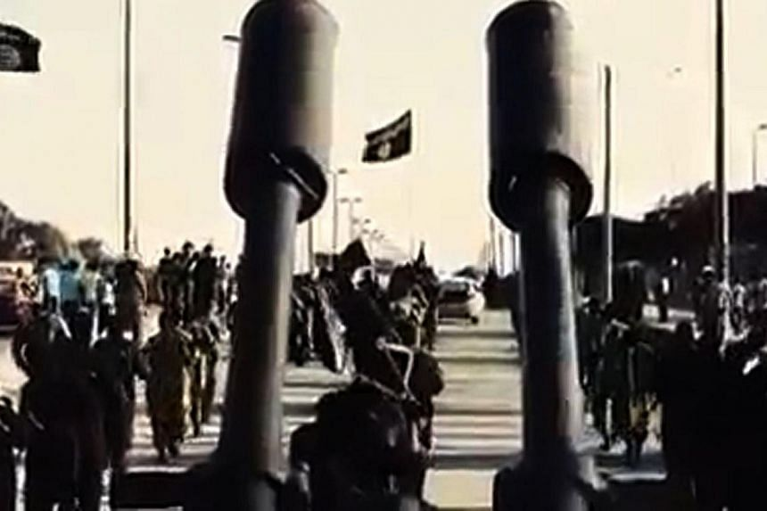 An image grab taken from a video released by Islamic State group's official Al-Raqqa site via YouTube on Sept 23, 2014, allegedly shows Islamic State in Iraq and Syria (ISIS) recruits marching in an unknown location.While ISIS is rapidly gainin