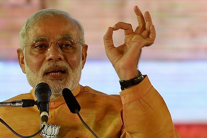 India Prime Minister Narendra Modi beefed up his government on Sunday, appointing 21 new ministers in a bid to speed up promised economic reforms after storming to power five months ago. -- PHOTO: AFP