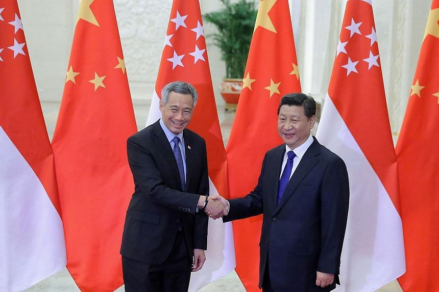 Singapore's Prime Minister Lee Hsien Loong (left) shakes hands with China's President Xi Jinping (right) during their meeting at the Great Hall of the People in Beijing on Nov 9, 2014. -- PHOTO: AFP