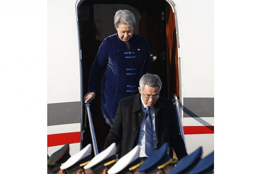 Singapore's Prime Minister Lee Hsien Loong and his wife Ho Ching arrive at the Beijing Capital International Airport Nov 9, 2014, to attend the Asia Pacific Economic Cooperation (APEC) meetings. -- PHOTO: REUTERS