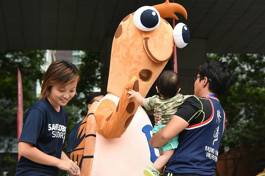 The Project Blue WaVe mascot, Bobby the hawksbill turtle, greeting a young spectator at the 32nd Singapore River Regatta 2014. -- PHOTO: PA WATER-VENTURE