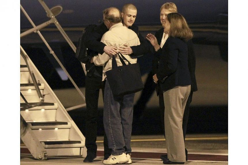 Matthew Todd Miller (centre, facing camera) reunites with his family members after he and Kenneth Bae (not pictured) landed aboard a US Air Force jet at McChord Field at Joint Base Lewis-McChord, Washington on Nov 8, 2014. -- PHOTO: REUTERS