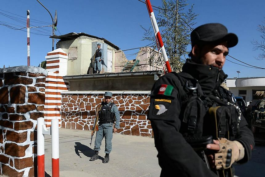 Afghan policemen stand guard at the entrance to police headquarters in Kabul on Nov 9, 2014.-- PHOTO: AFP