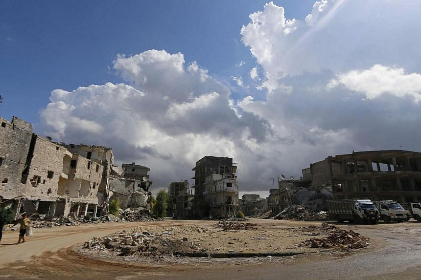 Civilians walk past damaged buildings in Aleppo's eastern district of Tariq al-Bab on Sept 28, 2014. -- PHOTO: REUTERS