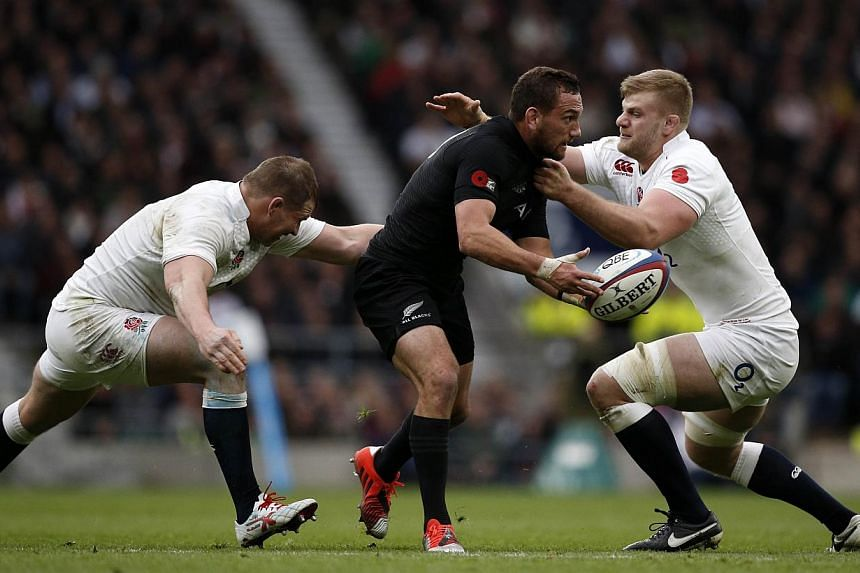 New Zealand's Aaron Cruden (centre) passes the ball as he gets tackled by England's Dylan Hartley (left) and George Kruis (right) during the Autumn international rugby union Test match between England and New Zealand at Twickenham Stadium on Nov 8, 2