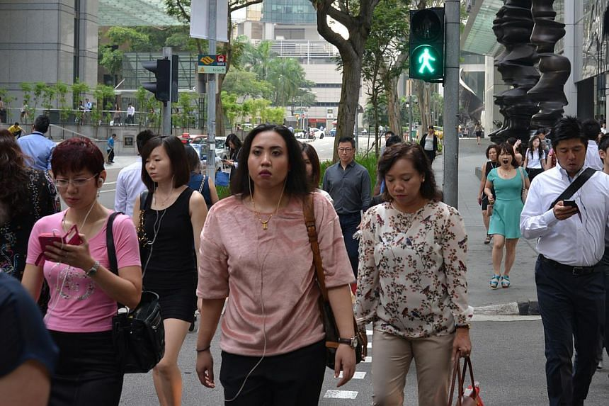 (Above) Pedestrians with their eyes glued to their gadgets are a common sight on the roads and pavements here. -- PHOTO: BENSON ANG