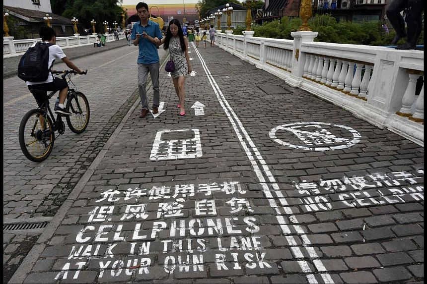 (Above) In Chongqing, China, there is a dedicated lane for mobile phone users. -- PHOTO: REUTERS