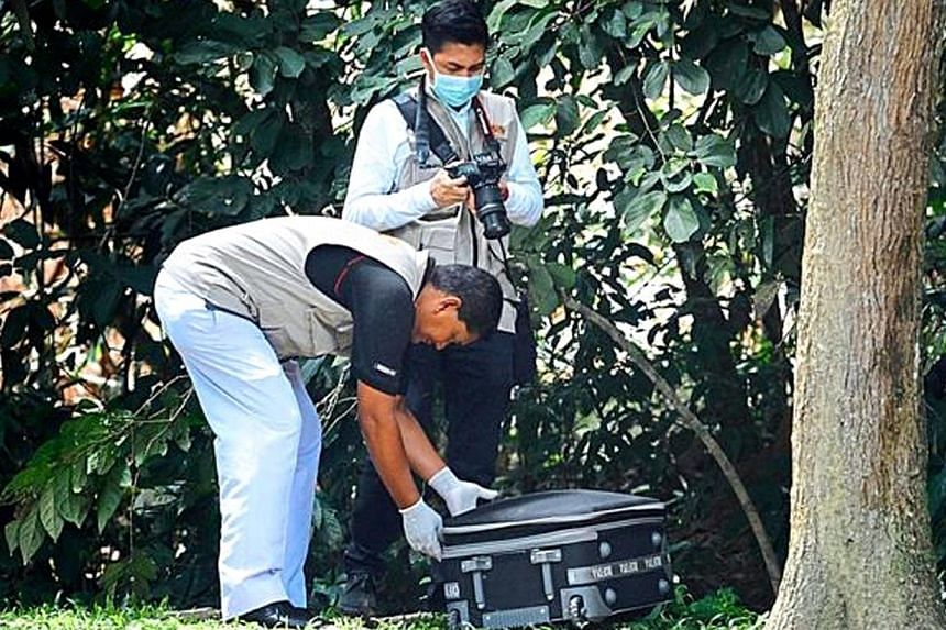 Penang Hospital forensic personnel taking a bag with body parts to the hospital for post mortem on Nov 7, 2014.-- PHOTO:THE STAR
