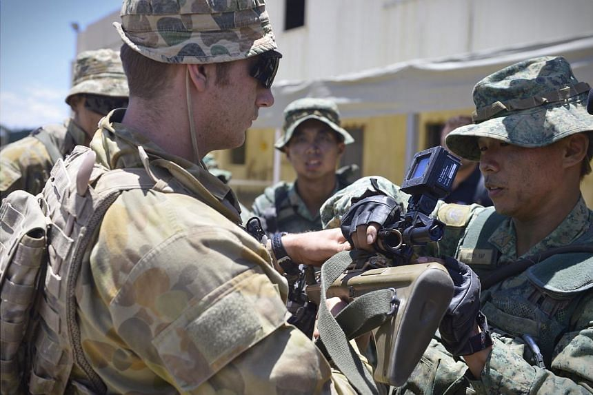Second Sergeant Jason Yap (right), 27, fits a round corner sensor on 22-year-old Private Jacob Damon's gun (left), during a Tactics, Techniques and Procedures (TTP) sharing session before performing a dry run of an urban-based exercise at the Urban O