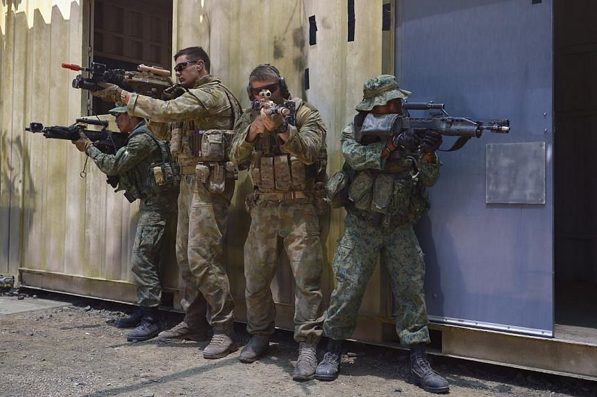 Soldiers from the Singapore Guards and the 7th Australian Regiment clear a room during a dry run of an urban-based exercise at the Urban Operations Training Facility in Shoalwater Bay Traning Area, Rockhampton, on Nov 9, 2014.-- ST PHOTO: MARK