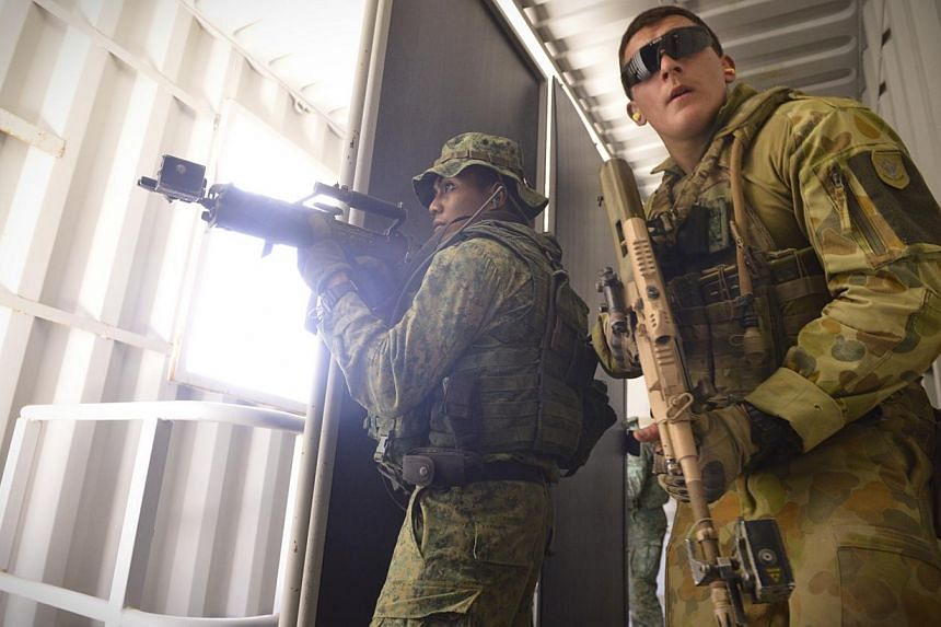 A soldier from the Singapore Guards (left) and the 7th Australian Regiment (right) clear a room during a dry run of an urban-based exercise at the Urban Operations Training Facility in Shoalwater Bay Traning Area, Rockhampton, on Nov 9, 2014. -- ST P