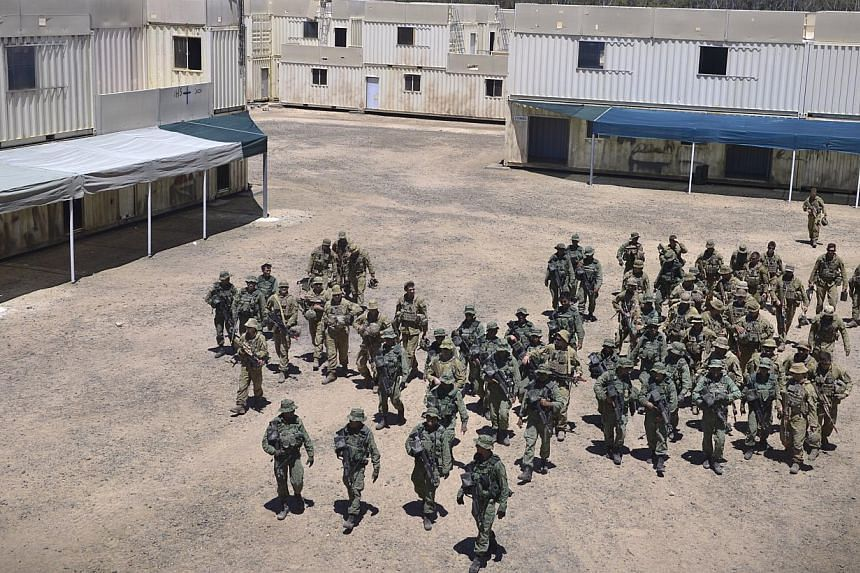 Soldiers from the Singapore Guards and the 7th Australian Regiment prepare to take a group photograph in the middle of performing dry runs of an urban-based exercise at the Urban Operations Training Facility in Shoalwater Bay Traning Area, Rockhampto