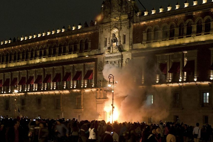 Demostrators set fire the door of the main entrance of te Mexican National Palace during a demostration in Mexico City on Nov 8, 2014, demanding justice from the Mexican goverment in the massacre of 43 missing students. -- PHOTO: AFP