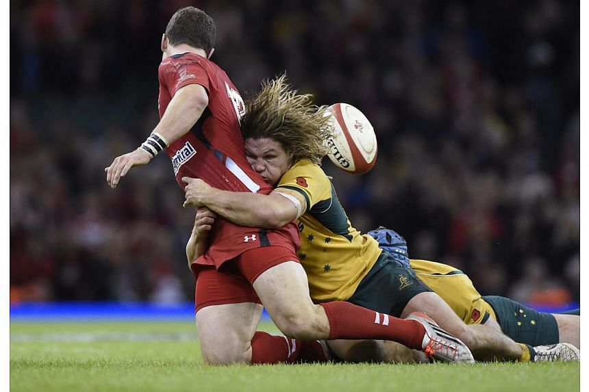 Wales' George North is tackled by Australia's Michael Hooper (right) during their Autumn International rugby union match at the Millennium Stadium in Cardiff, Wales, Nov 8, 2014. Australia edged Wales 33-28 to extend Wales' losing streak to southern