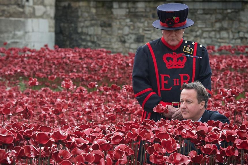 "A Yeomen Warder stands by as British Prime Minister David Cameron plants a poppy in the ""Blood Swept Lands And Seas Of Red"" installation by ceramic artist Paul Cummins and theatre stage designer Tom Piper, marking the centenary of the outbreak of the"