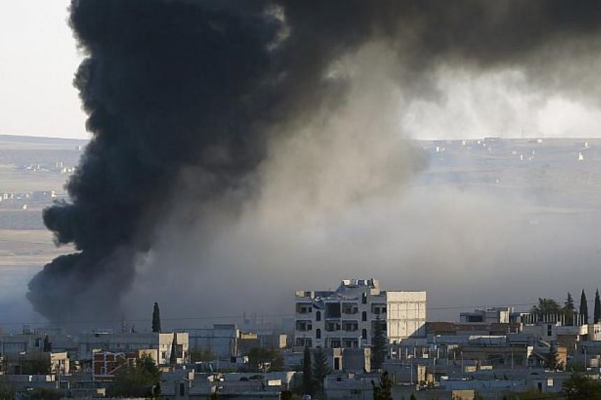 Thick black smoke rises over an eastern Kobane neighbourhood following an airstrike on Nov 8, 2014. Picture taken from the Turkish side of the Turkey-Syria border. US-led air strikes have targeted a gathering of Islamic State leaders in Iraq in a tow