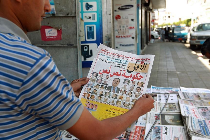 A Yemeni man reads a daily newspaper headline announcing the formation of a new government headed former oil minister Khalid Bahah, on Nov 8, 2014, in the capital Sanaa. Al-Qaeda claimed on Saturday that its militants killed dozens of Shi'ite re