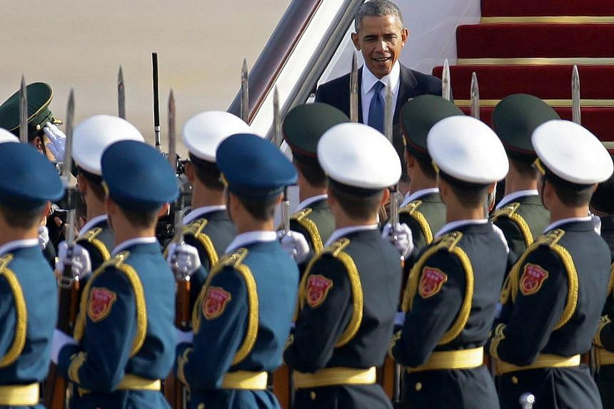 Honour guards saluting as US President Barack Obama steps from Air Force One upon his arrival in Beijing, on Nov 10, 2014. -- PHOTO: REUTERS