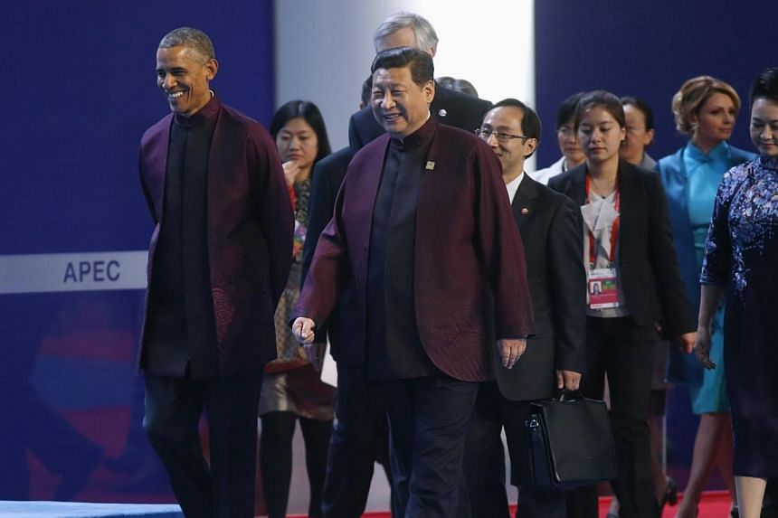 US President Barack Obama and Chinese President Xi Jinping walk ahead of other leaders as they arrive for the Apec Summit family photo in Beijing on Nov 10, 2014. -- PHOTO: REUTERS