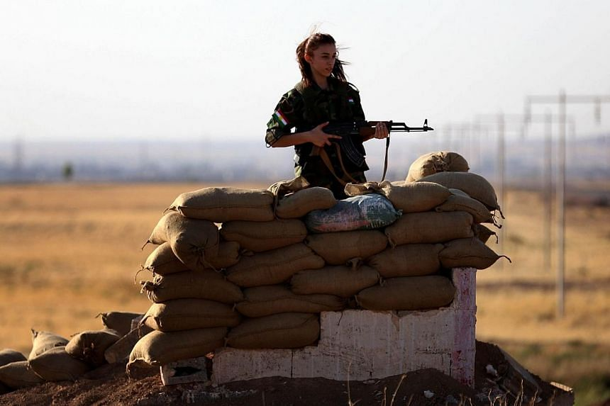 An Iranian Kurdish female member of the Freedom Party of Kurdistan (PAK) keeps a position in Dibis, some 50 kms northwest of Kirkuk, on Sept 15, 2014. Iran said on Monday that it was at Iraq's disposal to help its neighbour battle the Islamic St