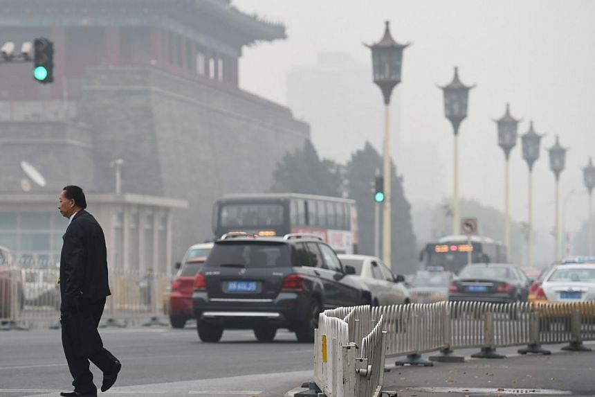 A man crosses a road on a polluted day in Beijing on Oct 20, 2014. Chinese President Xi Jinping has been checking Beijing's pollution first thing every morning, he told world leaders Monday, after authorities pulled out all the stops to avoid th