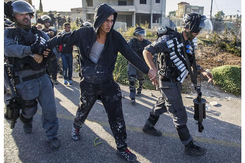 Israeli security forces detain an Arab-Israeli youth during clashes in the town of Kfar Kana, in northern Israel on Nov 9, 2014, a day after security forces shot dead a 22-year-old Arab-Israeli man.A Palestinian stabbed and critically wounded a