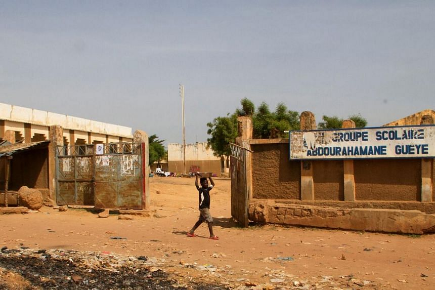 A child walks on Oct 26, 2014, past a school that was closed after the first confirmed Ebola patient in Mali died on Oct 24 in Kayes, west of the Malian capital of Bamako.Mali is preparing to release 108 people from Ebola quarantine in a tentat