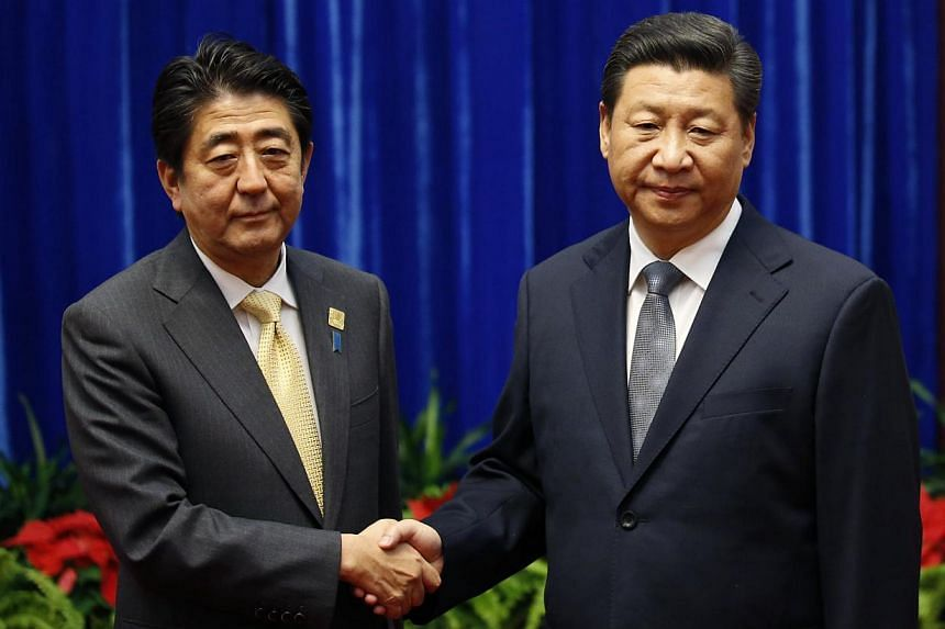This is the main photo in a series of shots early on Monday that got political watchers commenting. China's President Xi Jinping (right) shakes hands with Japan's Prime Minister Shinzo Abe during their meeting at the Great Hall of the People, on the
