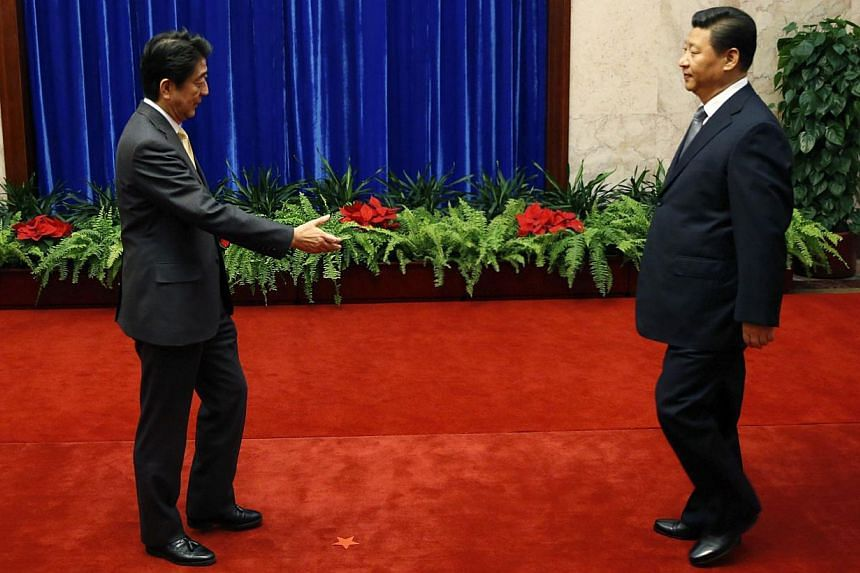 As they approach each other, Japan's Prime Minister Shinzo Abe extends his hand early before reaching China's President Xi Jinping (right) but the latter is a little slow himself. -- PHOTO: REUTERS
