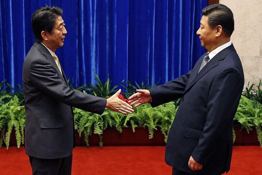 Japan's Prime Minister Shinzo Abe (left) is about to shake hands with China's President Xi Jinping (right). -- PHOTO: REUTERS