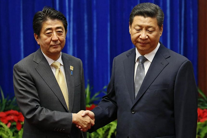 China's President Xi Jinping (right) shakes hands with Japan's Prime Minister Shinzo Abe during their meeting at the Great Hall of the People, on the sidelines of the Asia Pacific Economic Cooperation (APEC) meetings, in Beijing on Nov 10, 2014. -- P