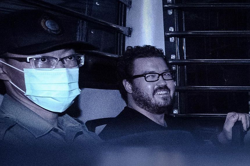 British banker Rurik Jutting, charged with the grisly murders of two women, smiles as he sits in a prison van leaving the eastern court in Hong Kong on Nov 10, 2014. Jutting's case was adjourned on Monday so that he could undergo psychiatric eva