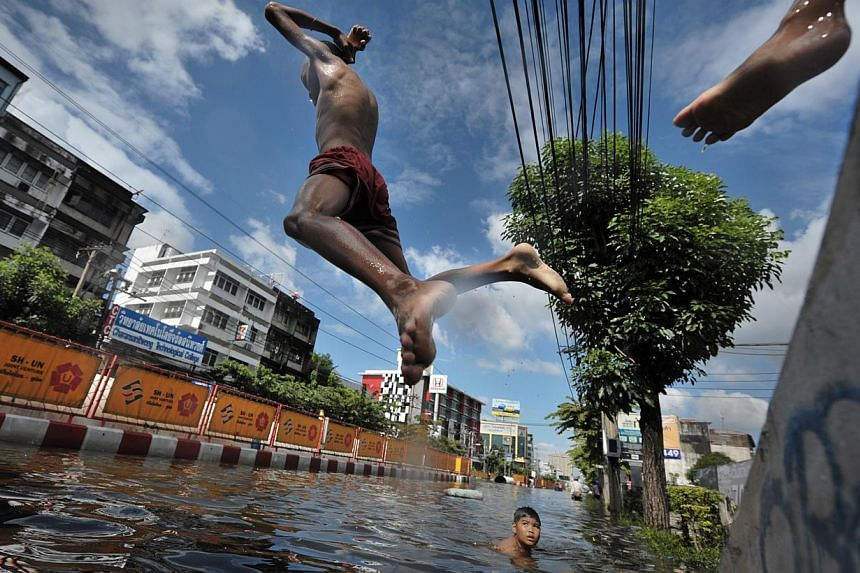 Children playing in a flooded district in Bangkok in October 2011. The Thai state's response to the floods reflected social and spatial injustices, as certain areas and people were protected or compensated more than others.