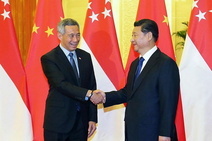 PM Lee Hsien Loong meeting Chinese President Xi Jinping at the Great Hall of the People in Beijing yesterday. Leaders of the 21-member Apec grouping are gathered in Beijing for the annual summit.