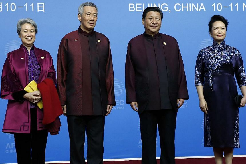 Singapore's Prime Minister Lee Hsien Loong (second left) and his wife Ho Ching pose for photographs with China's President Xi Jinping (second right) and his wife Peng Liyuan, during the Apec Welcome Banquet at Beijing National Aquatics Center, or the