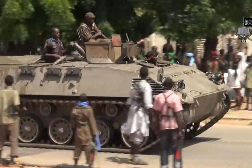 A screengrab taken on Nov 9, 2014, from a new Boko Haram video released by the Nigerian Islamist extremist group shows Boko Haram fighters parading on a tank in an unidentified town.A suicide bomb attack killed 47 students and injured 79 others
