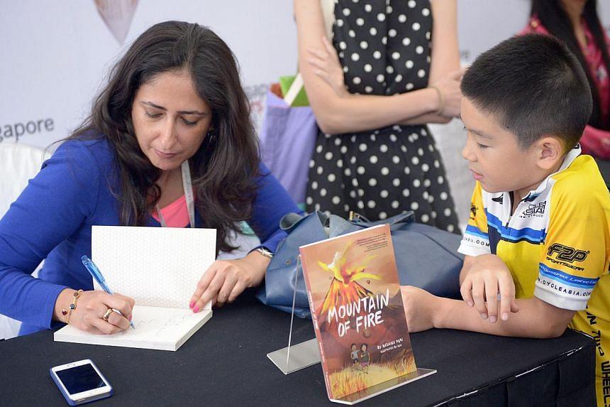 Writer Radhika Puri signing books at the Singapore Writers Festival on Nov 9, 2014.-- ST PHOTO:LIM SIN THAI