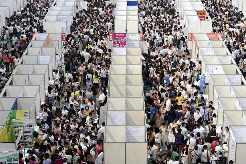 Thousands of job seekers visit booths at a job fair in China's Chongqing municipality. -- PHOTO: REUTERS