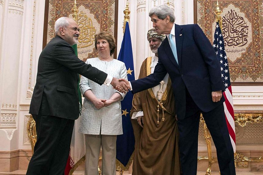 US Secretary of State John Kerry (right) and Iranian Foreign Minister Javad Zarif (left) shake hands as Omani Foreign Minister Yussef bin Alawi (second from right) and EU envoy Catherine Ashton watch in Muscat on Nov 9, 2014. -- PHOTO: REUTERS