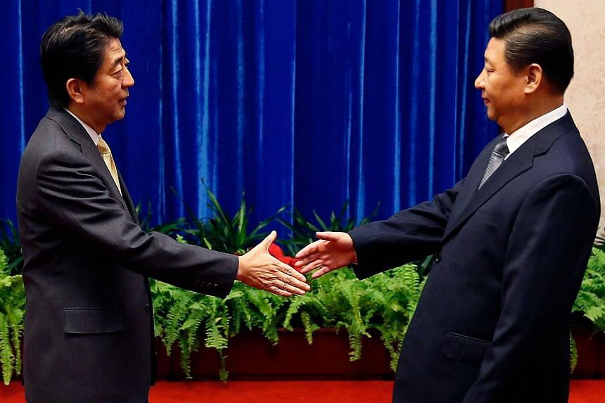 Japan's Prime Minister Shinzo Abe (left) shakes hands with China's President Xi Jinping during their meeting at the Great Hall of the People on the sidelines of the Asia-Pacific Economic Cooperation Summit in Beijing on Nov 10, 2014. -- PHOTO: AFP