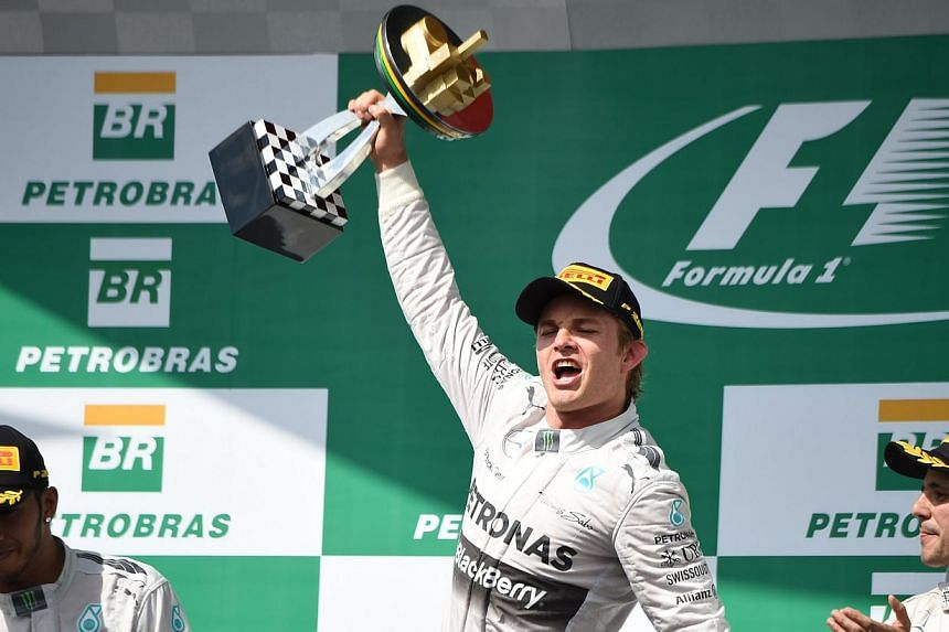 Mercedes AMG Petronas German driver Nico Rosberg (centre), flanked by teammate Lewis Hamilton (left) and Ferrari's Felipe Massa (right), celebrates on the podium after winning the Brazilian Formula One Grand Prix at the Interlagos racetrack in Sao Pa