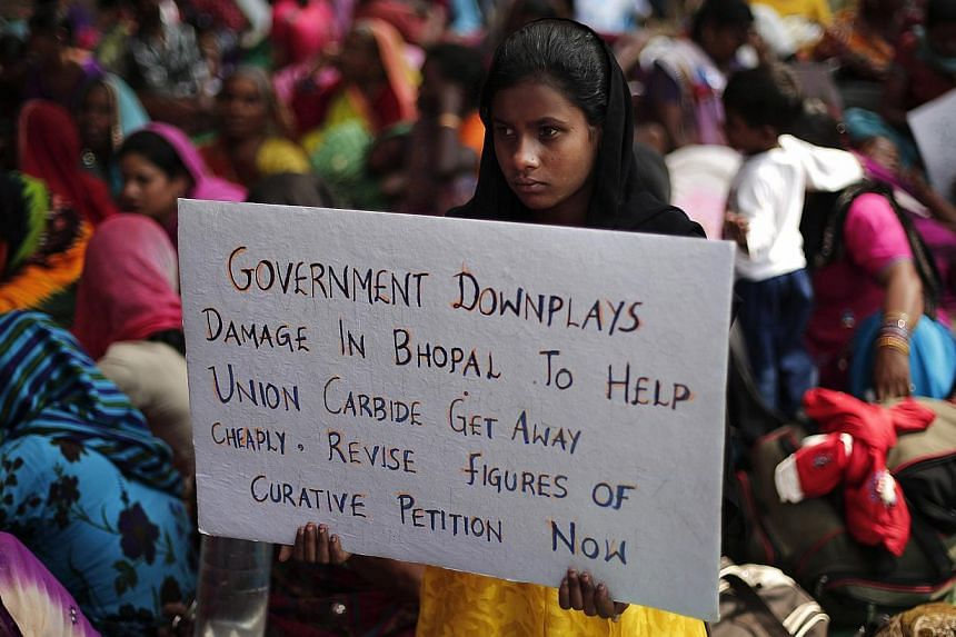 A child of a victim of the Bhopal gas tragedy, a gas leak from a Union Carbide pesticide plant that killed at least 3500 people, holds a placard during a sit-in protest in New Delhi on Nov 14, 2014. Hundreds of the victims held a sit-in protest and f
