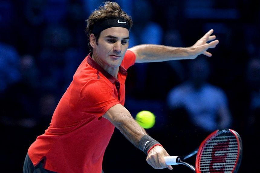 Switzerland's Rodger Federer returns to Canada's Milos Raonic during their singles group B match on the first day of the ATP World Tour Finals tennis tournament in London on Nov 9, 2014. -- PHOTO: AFP